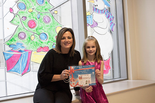 Angela Zangari Niagara Health's Executive Vice President Finance, Operations and Chief Financial Officer, presenting the Holiday Card Contest grand prize certificate to Alexa Kirkwood of Fonthill.